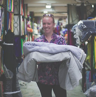 Photo of Samantha Jones founder of Little Yellow Bird, holding fabric in her arms