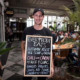 Photo of Nick Loosely founder of Everybody Eats holdin up a chalkboard sign outside his restaurant, smiling