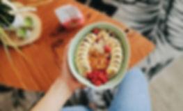 Une jeune femme tient dans ca main un bol de porridge sans gluten garnis avec de la banane, franboise et du beurre de cacahuète. Miam!