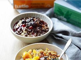 Scène petit-déjuner appetissante. Deux bols de porridges avec des fruits. Deux boites de porridge Turtle en arrière fond.