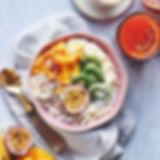 Un bol de porridge bio Turtle, garnis de fruits frais et servi avec un verre de jus. Les couleurs sont belles et la photo donne envie de manger un bon bol de porridge.