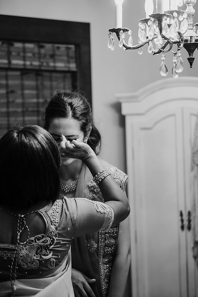 A young smiling woman and he friend prepare for he wedding.
