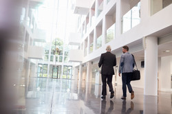 rear-view-of-businessmen-walking-through-office-P7JDNJK