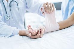 Close-up doctor is bandaging upper limb
