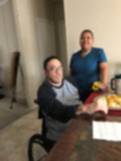 Female caregiver providing companionship for her male client who is in a wheelchair