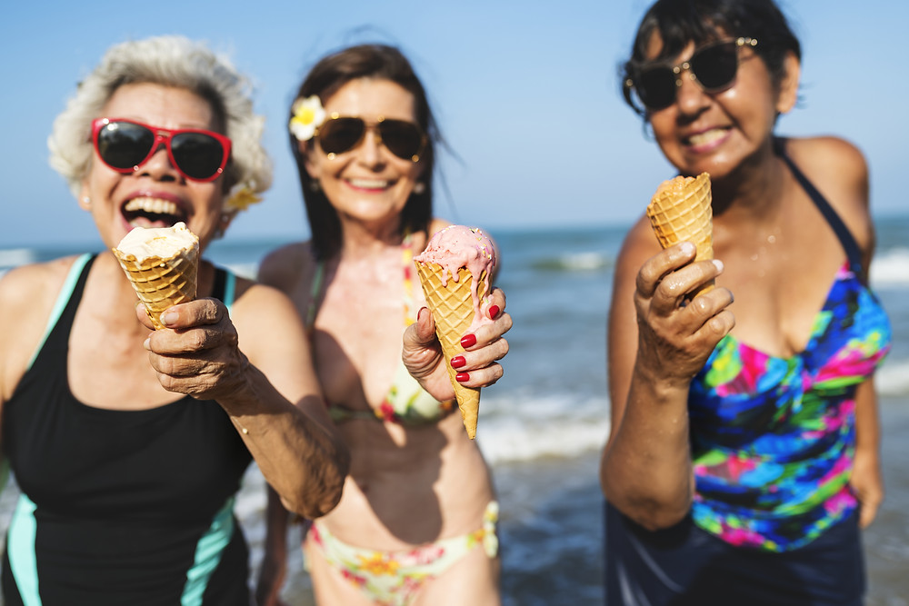 A group of senior women are enjoying the sun by keeping cool in fresh water and having fun eating ice cream. That's how you keep cool while keeping cool ;)