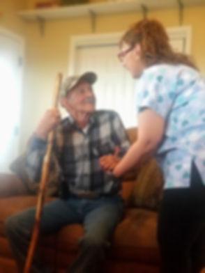 female caregiver helping elderly man stand up