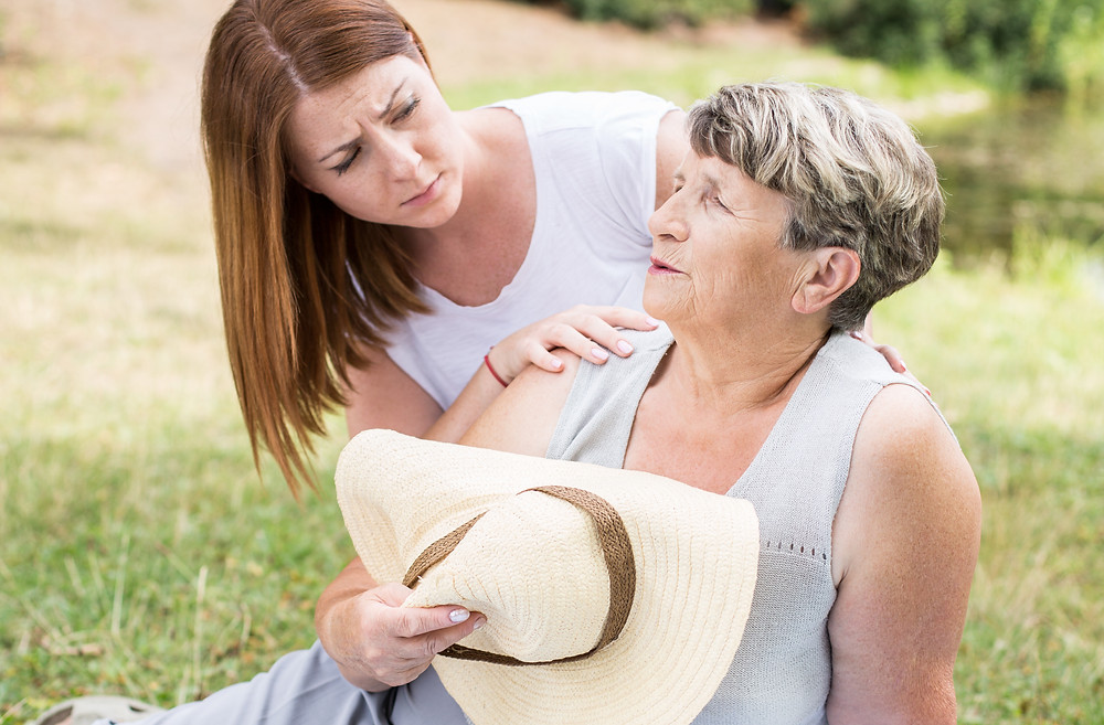 A senior women is experiencing heat-related illness symptoms and is resting while help is on the way.