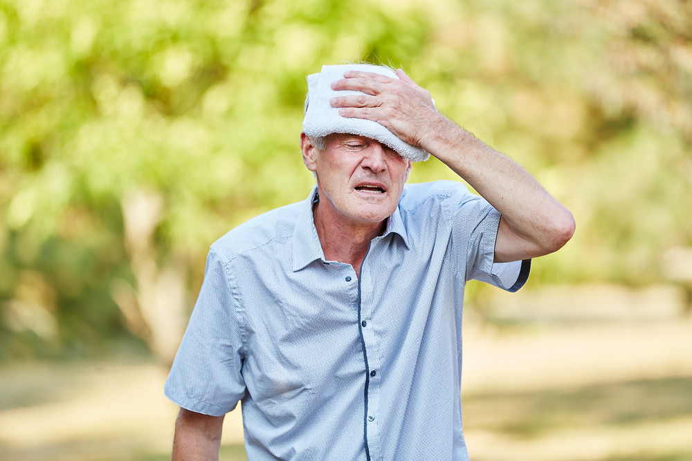 A senior man is trying to cool himself while walking outdoors in the summer heat.