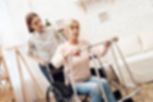 female caregiver helping elderly female stand up from wheelchair to her walker.
