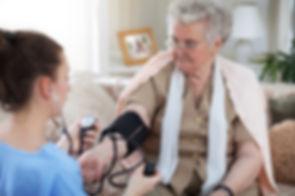 Home Health Care Nurse checking blood pressure of senior medicare insured patient