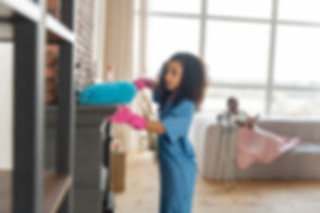 Female caregiver doing light cleaning and household chores at the home of her client