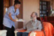 female caregiver preparing a healthy meal for elderly male patient
