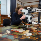 """Ellen Hanspach-Bernal, conservator of paintings at the DIA, studies """"The Wedding Dance"""" under magnification. Images taken with a camera attached to the microscope are referred to as """"photomicrographs"""" and can help document details, textures and conditions that are not obvious to the naked eye! Look at how Bruegel hinted at fingernails and painted tiny buttons in the first photomicrograph. Also, see how he depicted different fabrics and materials in the second and third. #WheresTheBruegel #PieterBruegelTheElder #artconservation"""