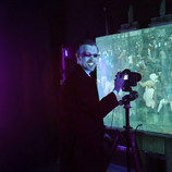 """Yesterday we showed how infrared light can be used to better understand paintings, and, today, we're focusing on ultraviolet (UV). In the first two photos, DIA Imaging Specialist and Photographer Aaron Steele is capturing an image of """"The Wedding Dance"""" under UV. _______________ When objects are exposed to UV, their atoms can become excited and release photons in the visible part of the electromagnetic spectrum. This is called fluorescence. Thus, this technique is called ultraviolet-induced visible fluorescence. The third image shows a detail of the fluorescence. Arrows highlight dark, non-fluorescent spots. These are small areas where there is no original paint and a conservator has added tiny dots of color to accommodate the losses. This painting is about 450 years old, so it does have some signs of age! The overall greenish cast is due to the fluorescence of the varnish. #WheresTheBruegel #PieterBruegelTheElder #artconservation"""