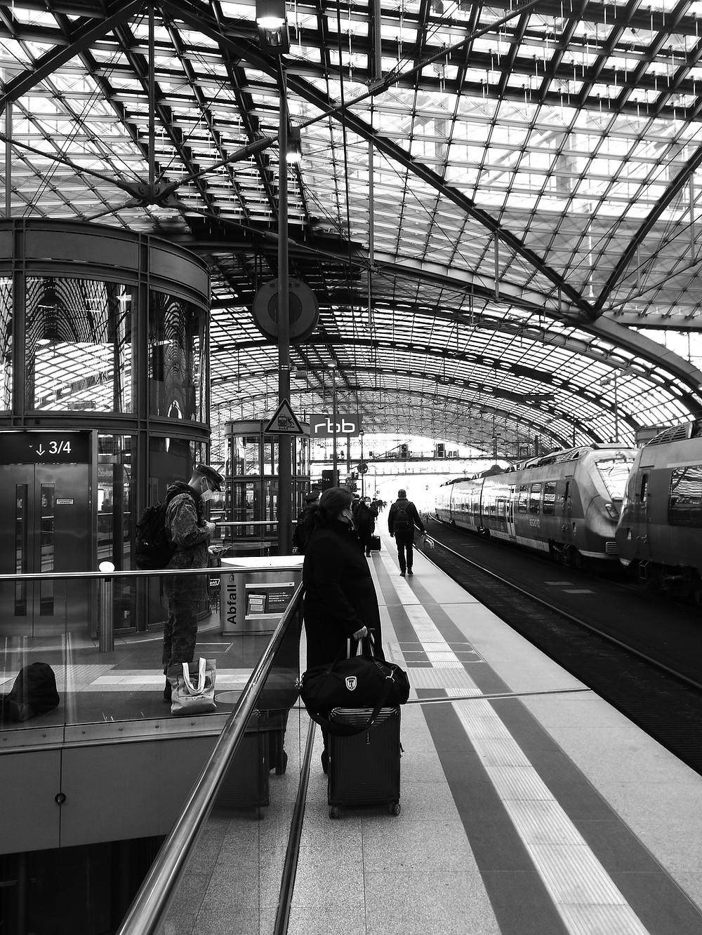 Ein Bundeswehrsoldat in Uniform wartet zwischen anderen Fahrgästen am Berliner Hauptbahnhof