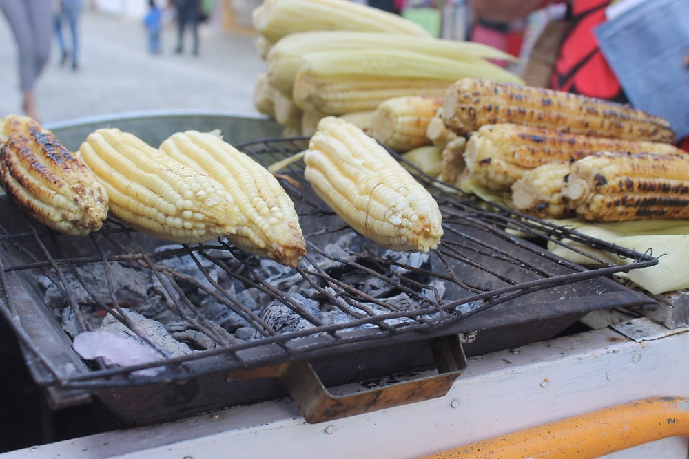Order an Elote - con límon, chile y sal (Corn with lime juice, chilli and salt) for a tasty street food snack!