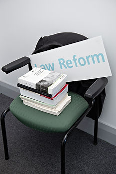 A work chair piled with reports and a sign that reads 'Law Reform'.