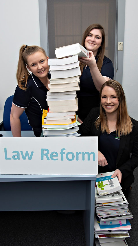 What a lot of reading: Members of the Law Reform Committee - Hannah, Tori and Kate - at a desk piled with legal reports.