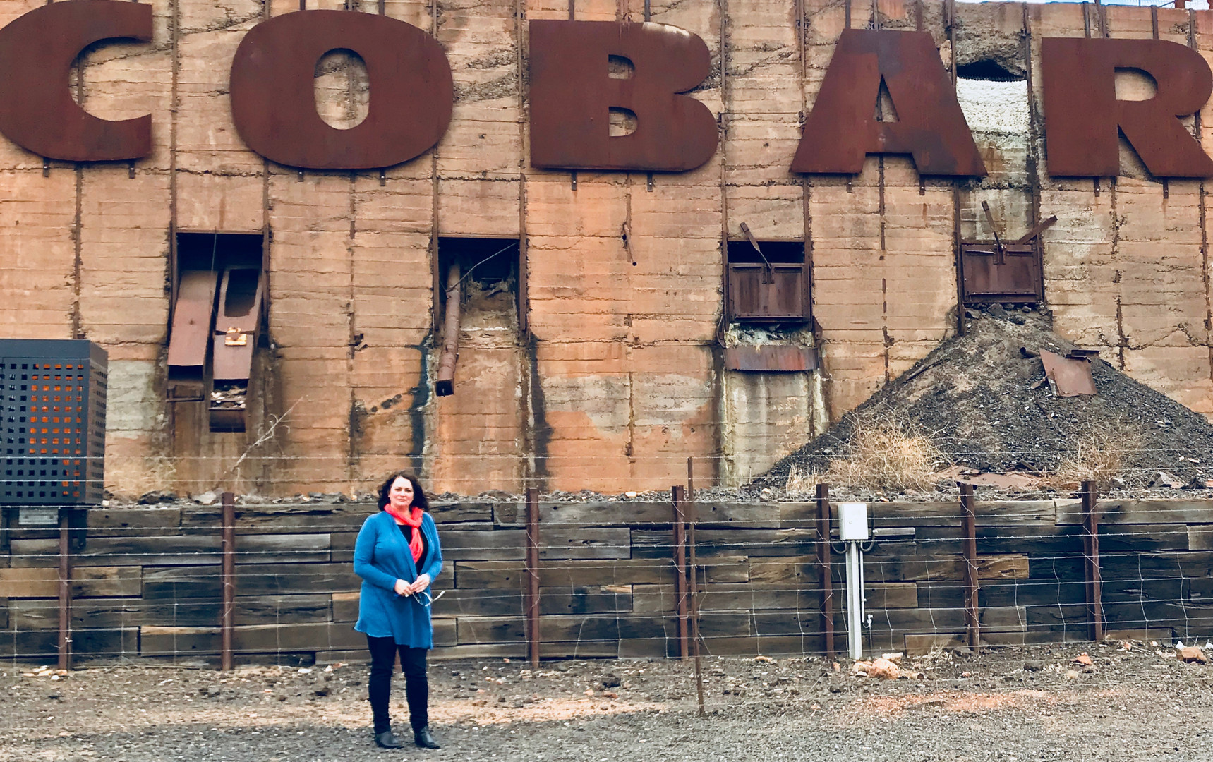 Western NSW Community Legal Centre solicitor, Tara, stands underneath a sign that reads 'Cobar'.