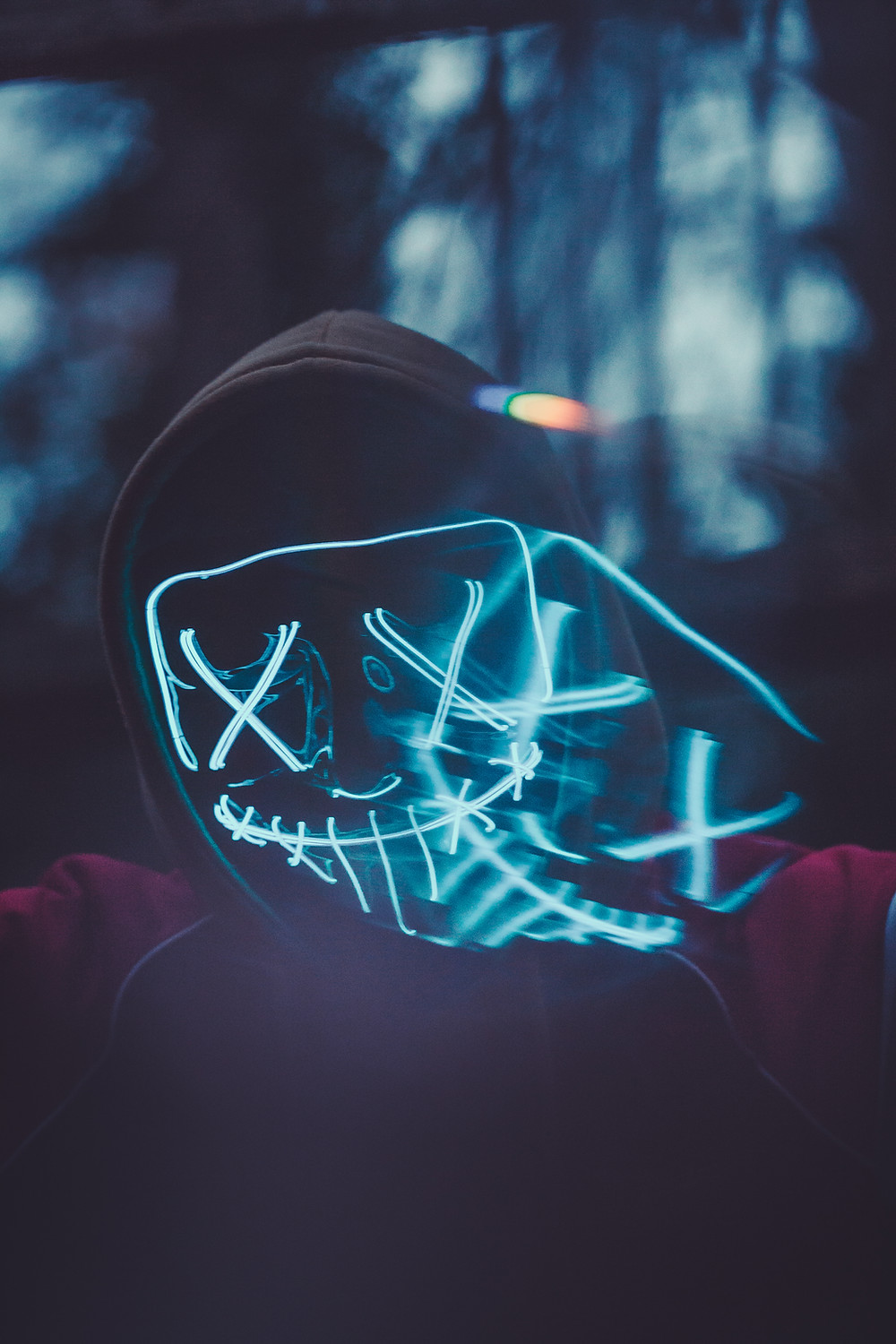 Lit up mask in a forest.