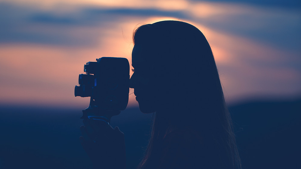 A woman takes a photo before the sun sets.