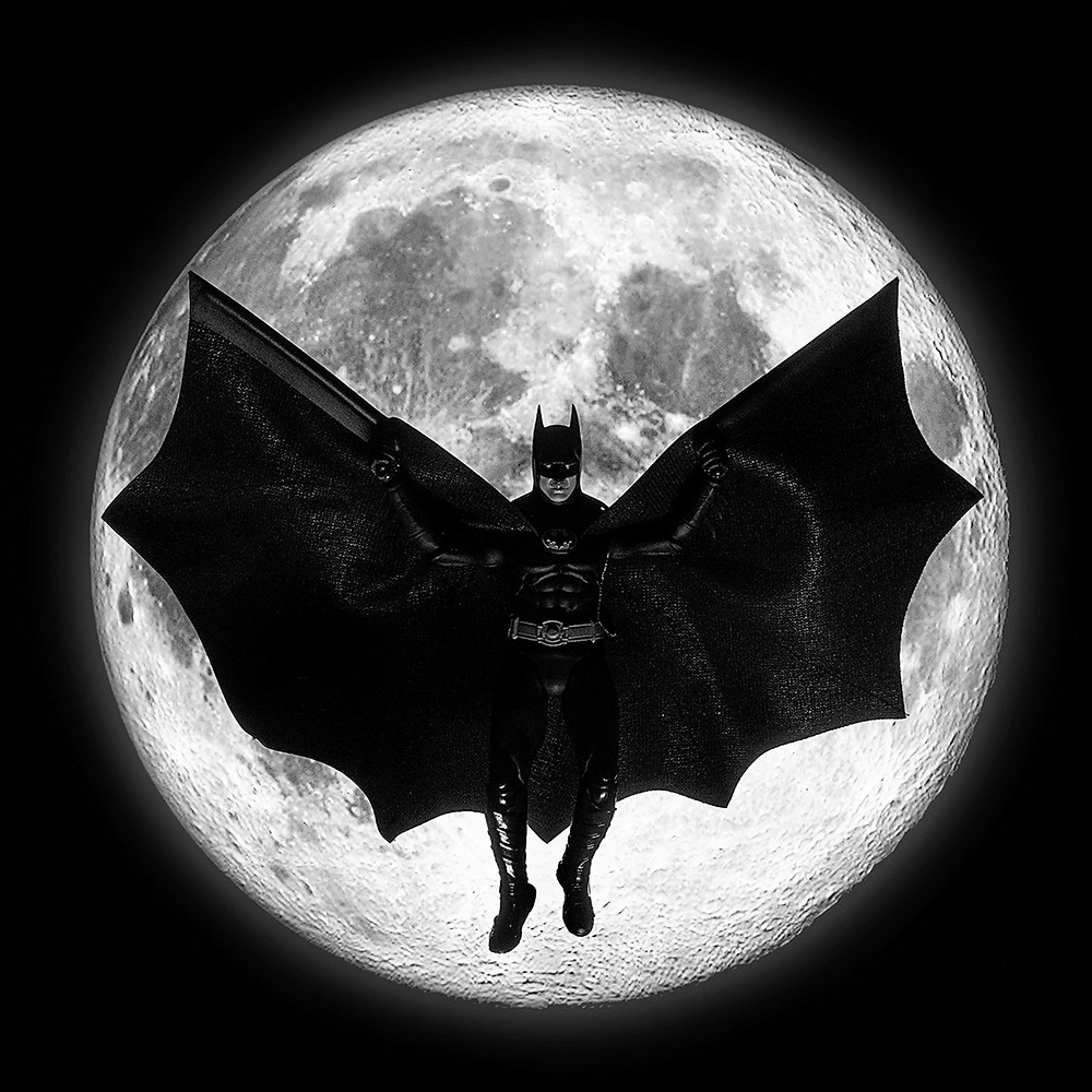 Tim Burton's Batman in front of a moon