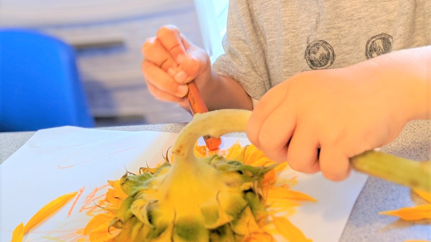 One of the students painting with flowers