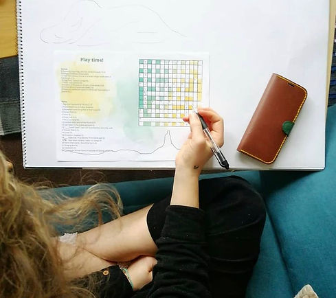 photograph from artist's perspective. right hand holds a pen, hovering above and starting a crossword.
