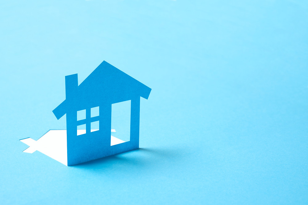A light blue house, cut out from paper