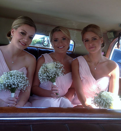 Three bridesmaids in wedding car with professional makeup artist in Lytham