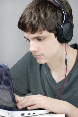 Close-up of a teen wearing headphones working on his laptop.jpg.jpg