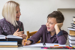 Junior student does homework with the help of his tutor.jpg
