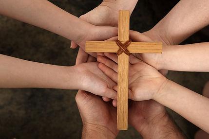 Our Faith - family hands holding cross.j