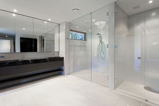 Image of a lovely modern bathroom with mirrors and shower screens provided by Wares