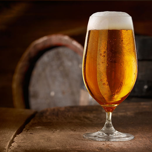 An image of a cool refreshing beer in a glass with a barrel in the background