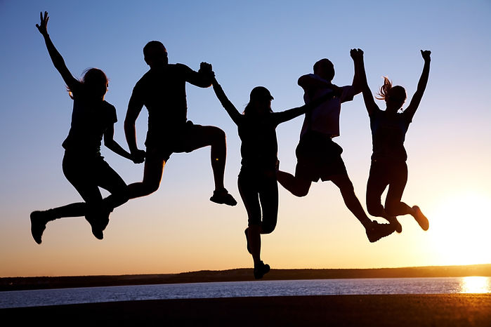 group of happy young people jumping at t