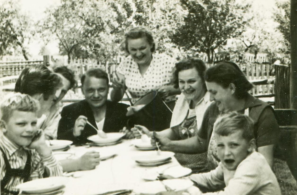 Old photo of a family eating soup outside