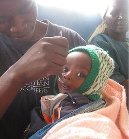 Malnurished child being fed