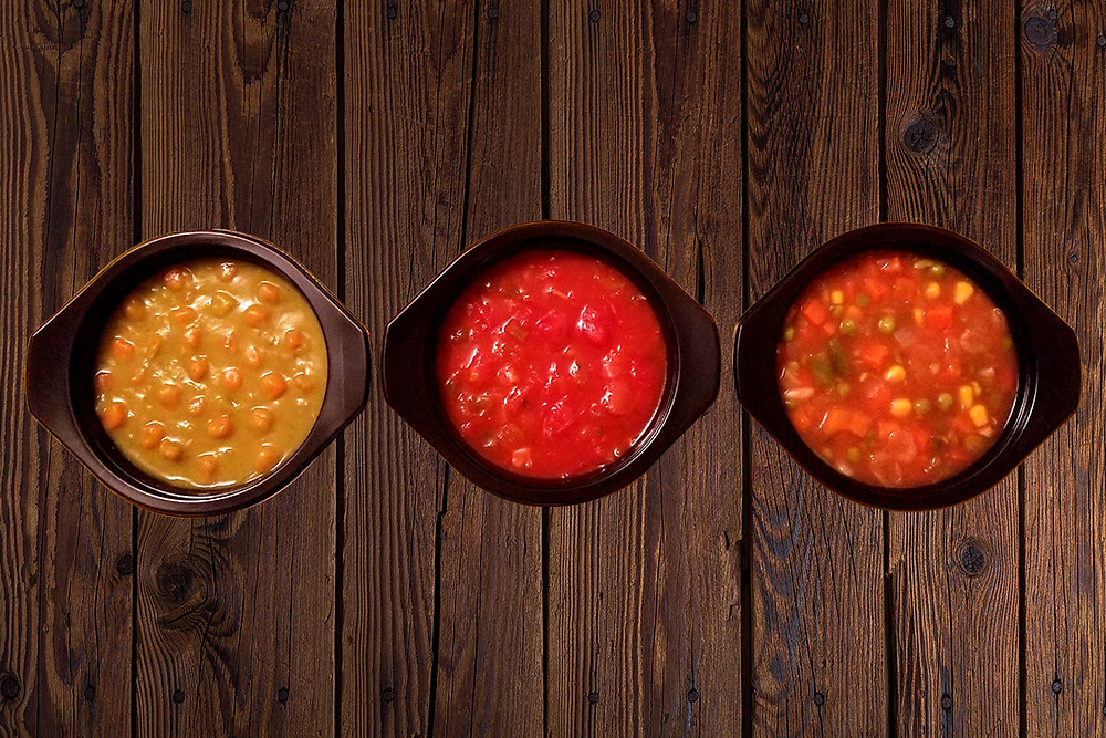 3 prepared Benje's Naturals soups on wooden background