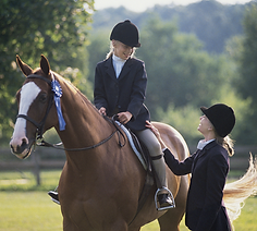 Teen sitting on a horse with instructor standing by