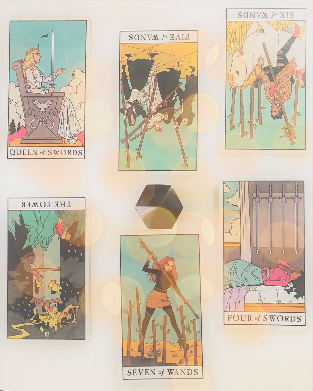 A spread of six tarot cards around a black crystal