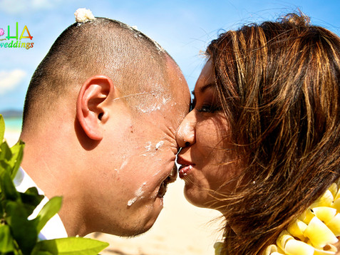 kissing the groom with cake on his face.