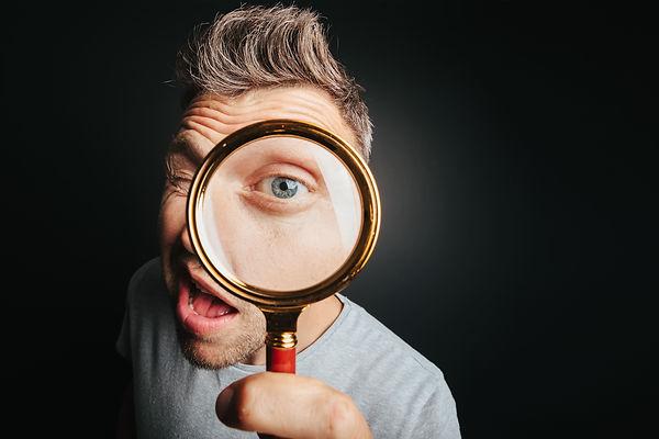 bigstock-man-see-through-magnifying-gla-381620408 (1).jpg