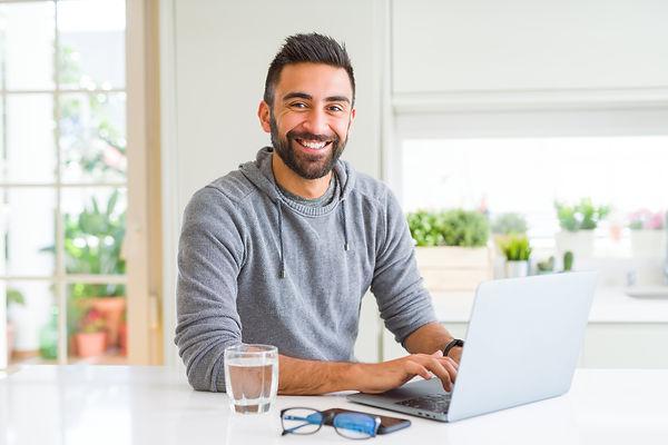 bigstock-Man-smiling-working-using-comp-