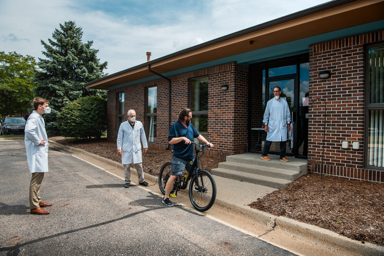 Todd testing his biking prosthesis outside the clinic with Jan, Fran, and Nick observing