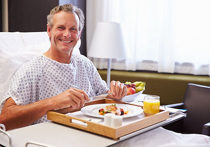 Male Patient In Hospital Bed Eating Meal From Tray.jpg