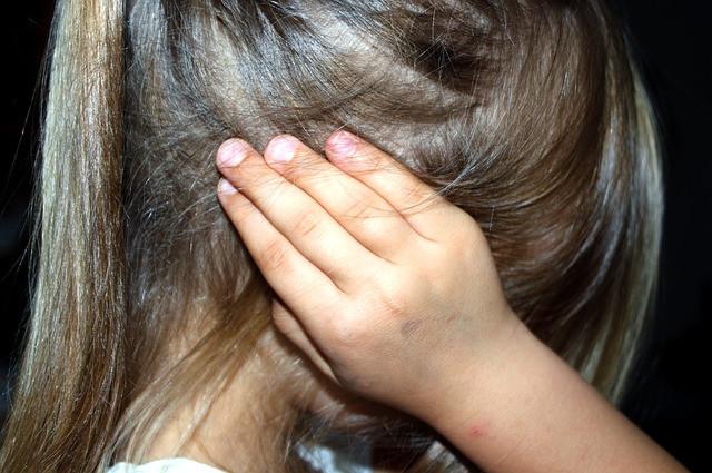 fetita cu mainile la urechi