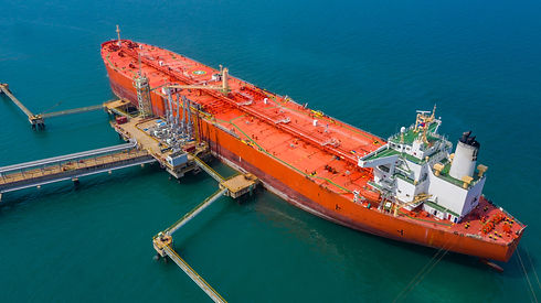 Red tanker ship loading and unloading oi