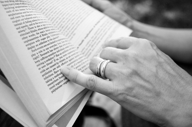 Close up of open book and hands holding it